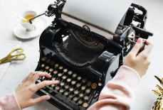woman uses black typewriter
