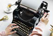 woman uses black typewriter